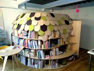 This bedroom bookhut (or igloo) was designed by Ben Nagaoka. Topped with a roof of felted tiles, shelves of books form a cozy reading wall around a hidden bed. In a survey titled Hot or Not, Apartment Therapy features more pictures of the book igloo, inside and out.